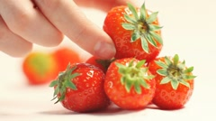 Hands puts strawberries on a white background Stock Footage