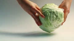 Hands takes cabbage on a white background - stock footage