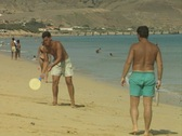 Stock Video Footage of Men playing ball and racket game on beach