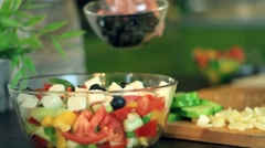 Female hands pouring oil into salad in glass bowl - stock footage