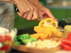 Female hands slicing yellow pepper, dolly shot Stock Footage