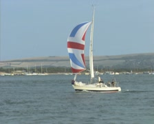 Passing sailing boat with colourful sail - stock footage