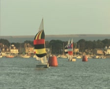 View of sailing boat with colourful sail from passing boat - stock footage