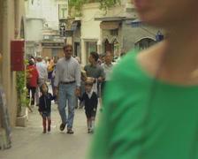 Pedestrians walking along road Stock Footage