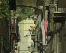 Zoom out from hanging laundry and passing cars in street Stock Footage