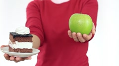Female hand offering tasty cake or healthy apple, isolated on white HD - stock footage