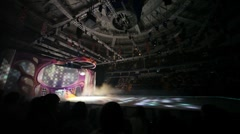 Actors in costumes skate on ice illuminated with colored lights in DS Megasport Stock Footage