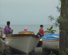 Little boys sitting on landed boats Stock Footage