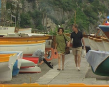Couple walking between landed boats Stock Footage