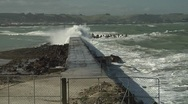 Small waves washing down seawall away from camera Stock Footage