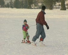Man pulling child along on skis Stock Footage