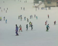 Zoom out from skiers to whole of piste Stock Footage