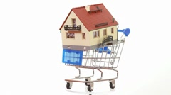 House model placed on shopping cart turning around on platform Stock Footage