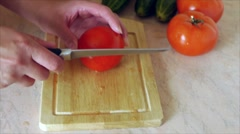 Young woman on kitchen table knifes tomato Stock Footage