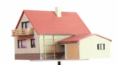 Little toy house turning around on transparent platform Stock Footage