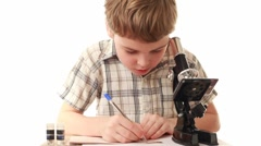 Boy sitting near microscope writes something in notebook Stock Footage