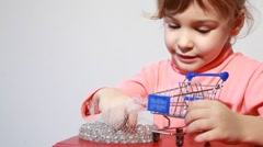 Little girl put white marbles in shopping cart model Stock Footage