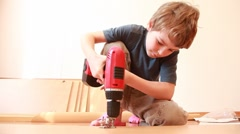 Boy use screwdriver while construct furniture element Stock Footage