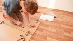 Little boy construct piece of wooden furniture on floor Stock Footage