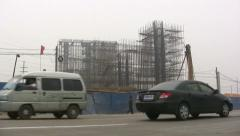 China, traffic passes construction site, heavy smog and pollution Stock Footage