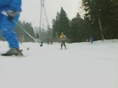 People skiing past ground level camera Stock Footage