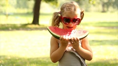 Little girl with sunglasses eat watermelon Stock Footage