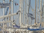 Greek flags attached to moored boats in harbour Stock Footage