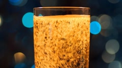 Glass of sparkling wine and color light in bokeh - stock footage