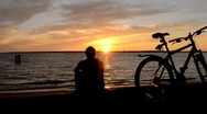Stock Video Footage of Man and Bicycle on the coast at sunset