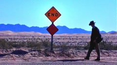 Cowboy in Sandy Desert Walks Past End Sign Stock Footage