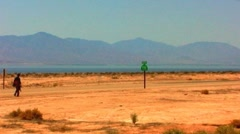 Cowboy Walks Desert Highway By Salton Sea Stock Footage