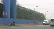 A Chinese worker passes a huge construction site on his tricycle Stock Footage