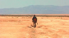Man Walks Away Across Dry Desert Plain Stock Footage
