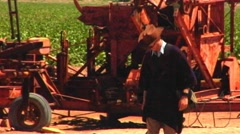 Man Walks Past Rusting Old Farm Machinery Stock Footage