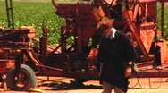 Stock Video Footage of Man Walks Past Rusting Old Farm Machinery 1