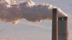 A power plant with smokestacks belches smoke into the air. Stock Footage