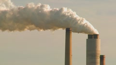 A power plant with smokestacks belches smoke into the air. - stock footage