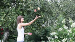 Pretty girl juggling with three apples - stock footage