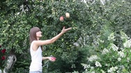 Stock Video Footage of Pretty girl juggling with three apples