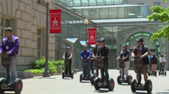 People ride segways in an outdoor area. Stock Footage