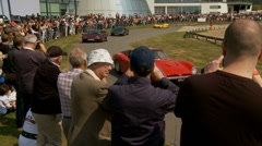 Spectators and super cars at Brooklands race track Stock Footage