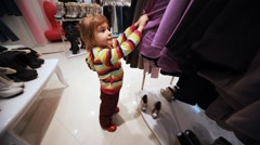 Stock Video Footage of girl carefully choose clothes in shop
