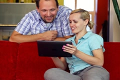 Young woman showing something to her man on tablet computer NTSC - stock footage