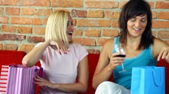 Two female friends with shopping bags sitting on the sofa HD Stock Footage