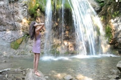 Woman with outstretched arms by the waterfall Stock Footage
