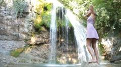 Woman in dress standing near a waterfall Stock Footage