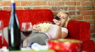 Woman lying on sofa, eating popcorn and watching tv HD Stock Footage