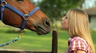 Pretty girl feeding her horse carrots Stock Footage