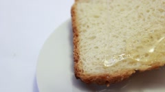 Pouring honey on a slice of bread _2 Stock Footage
