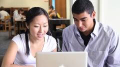 Asian Female and African American Male Students in the Library - stock footage